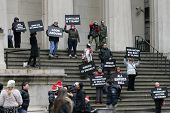 NEW YORK - DEC 19: Protestors hold signs while standing on the steps of Federal Hall in lower Manhat