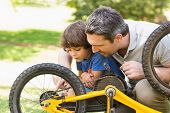 Side view of father and son fixing bike