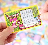 BOISE, IDAHO - DECEMBER 21, 2013: A Lucky 7 scratch ticket being played in hopes of winning a cash p