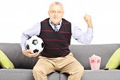 Middle aged sport fan holding a soccer ball and watching sport isolated on white background