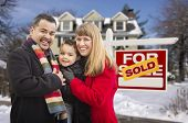 Warmly Dressed Young Mixed Race Family in Front of Sold Home For Sale Real Estate Sign and House with Snow On The Ground.