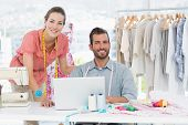 Male and female fashion designers with laptop at work in a bright studio