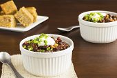 stock photo of jalapeno  - Vegetarian chili made with onions tomatoes corn kidney and black beans topped with sour cream and diced jalapeno served with cornbread - JPG