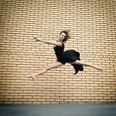 Attractive teen girl dancing outdoor against brkics wall. Toned.