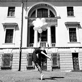 Attractive teen girl dancing with balloons outdoor against old building. Black and white.