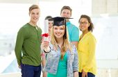 education and people concept - smiling female student with diploma and corner-cap and friends on the back