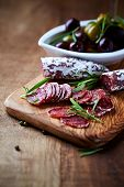 Mediterranean Sausage with Rosemary on a Wooden Chopping Board