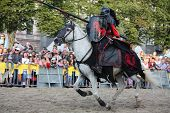 Riga, Latvia - August 21: Gerard Naprous From The Devils Horsemen Stunt Team Riding White Horse Duri