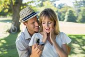 stock photo of propose  - Man surprising his girlfriend with a proposal in the park on a sunny day - JPG