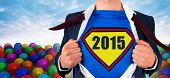 Businessman opening shirt in superhero style against many colourful balloons against sky