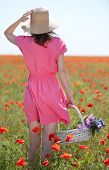Beautiful young woman holding wicker basket in poppy field