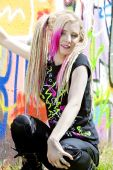 foto of teenage girl  - portrait of young woman sitting at graffitti wall - JPG