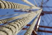 picture of tall ship  - Close view of aged rope rigging of a tall ship sailing mast over blue clear sky - JPG