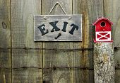 Exit sign over barbed wire fence post with red barn birdhouse