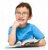 Cute little boy is reading a book while wearing glasses supporting his head with hand, isolated over white