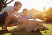 stock photo of aeroplan  - son and dad playing with toy aeroplane in the garden at home having fun together and smiling - JPG