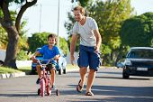 father teaching son learning to ride bicycle boy