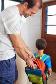 Father packing school lunch into son backpack before he goes to learn