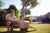 son and dad playing with toy aeroplane in the garden at home having fun together and smiling