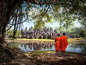 Angkor Wat monk. Ta Prohm Khmer ancient Buddhist temple in jungle forest. Famous landmark, place of