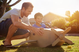 pic of aeroplan  - son and dad playing with toy aeroplane in the garden at home having fun together and smiling - JPG