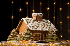 stock photo of gingerbread house  - Beautiful gingerbread house with lights on dark background - JPG
