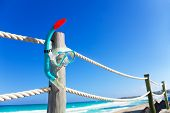 Snorkeling mask on wooden pier with white ropes
