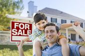 Mixed Race Father and Son Piggyback in Front House and For Sale Real Estate Sign.