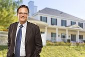 Attractive Businessman In Front of Beautiful New Residential Home.
