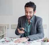Young man wearing jacket sitting in restaurant and looking on phone.