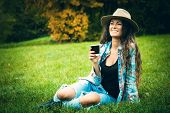 smiling young woman enjoy in coffee break in nature, sit in grass in park, wearing blue torn jeans and tartan shirt, full body shot