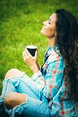 smiling young woman enjoy in coffee break in nature, sit in grass in park, wearing blue torn jeans and tartan shirt, profile