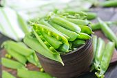 picture of snow peas  - green pea on the wooden board and on a table - JPG
