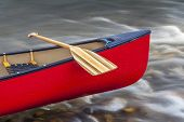 red canoe bow with a wooden paddle against a shallow river rapid
