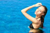 Close up Sensual Pretty Woman in Black Swim Wear Posing at Enchanting Swimming Pool on a Tropical Climate.