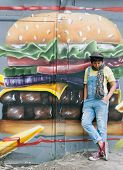 Toung woman standing near wall covered with graffiti of cheeseburger