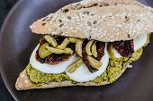 Gourmet sandwich with pesto sauce and olives