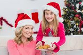 Festive mother and daughter with plate of cookies at home in the living room