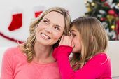 Daughter telling her mother a christmas secret at home in the living room