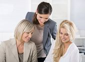 Successful team of well educated businesswoman sitting at desk wearing business outfit.