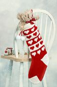 Teddy bear in Christmas stocking on back of chair