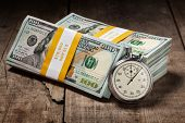 Time is money loan debt deadline concept background - stopwatch and stack of new 100 US dollars 2013 edition banknotes (bills) bundles on wooden background