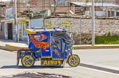 PUNO, PERU, MAY 5, 2014: Auto rickshaw drives down the street in proximity of Puno port