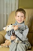 Little Boy Feeds Medicinal Syrup The Toy Dog And Looking At Camera