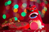 Chinese new year decorations, miniature dancing lion and firecrackers on red glitter background.