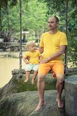 Baby and father are sitting on a swing