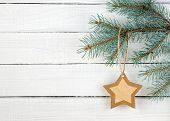 Paper Christmas Star On Spruce Branch On Wooden Background