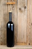 Wine Bottle With Corkscrew On Old Wooden Background