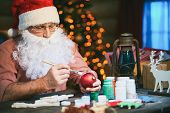 Senior man in Santa cap and beard painting toy balls with gouache
