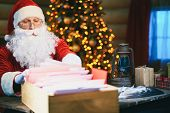 picture of letters to santa claus  - Santa Claus looking through Christmas letters - JPG